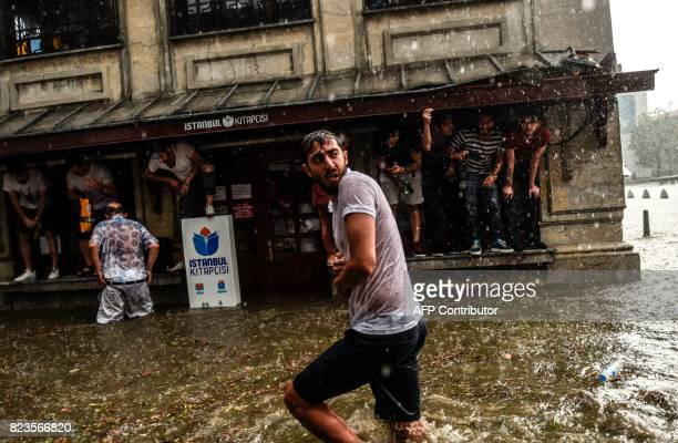 TOPSHOT A pedestrian walks past as bystanders shelter perched on a building during a heavy downpour of rain and hail at Besiktas near Istanbul on...