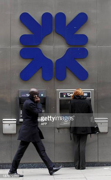 A pedestrian walks past ATM machines of the Royal Bank of Scotland as a customer uses one in London on January 30 2012 The chief executive of...