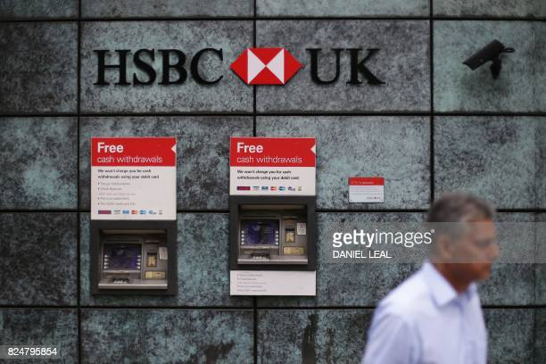 A pedestrian walks past automated teller machines outside a branch of a HSBC bank in the City of London on July 31 2017 HSBC said profits were up in...