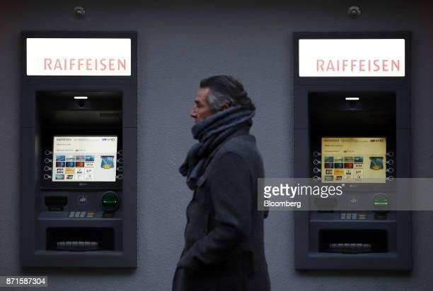 A pedestrian walks past automated teller machines outside a Raiffeisen Schweiz Genossenschaft bank branch in Bern Switzerland on Tuesday Nov 7 2017...