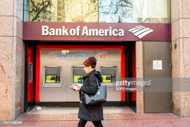 A pedestrian walks past Bank of America ATMs