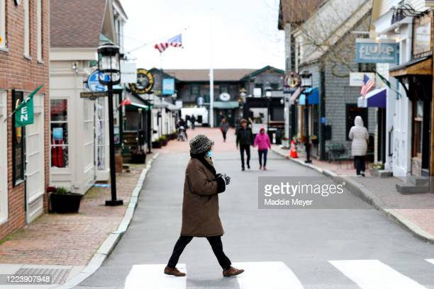 Pedestrian walks past Bannister's Wharf on May 09, 2020 in Newport, Rhode Island. Non-critical retail establishments began opening their doors with...