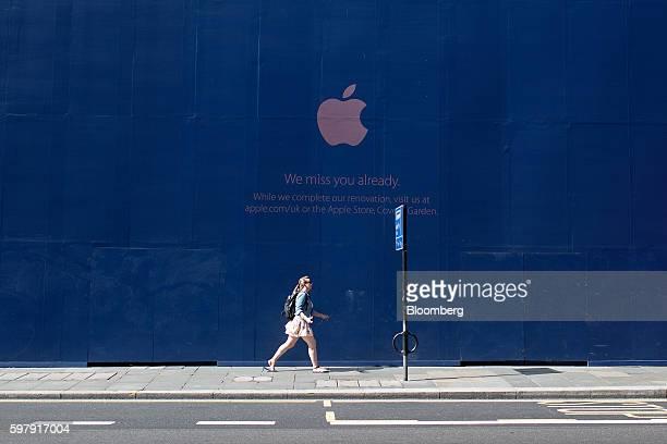 Pedestrian walks past boarding outside an Apple Inc. Store as the shop undergoes renovation work on Regent Street in London, U.K., on Tuesday, Aug....