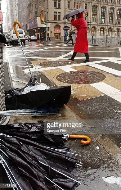 A pedestrian walks past broken umbrellas October 16 2002 in New York City A strong storm brought a high wind warning and heavy rains to the New York...
