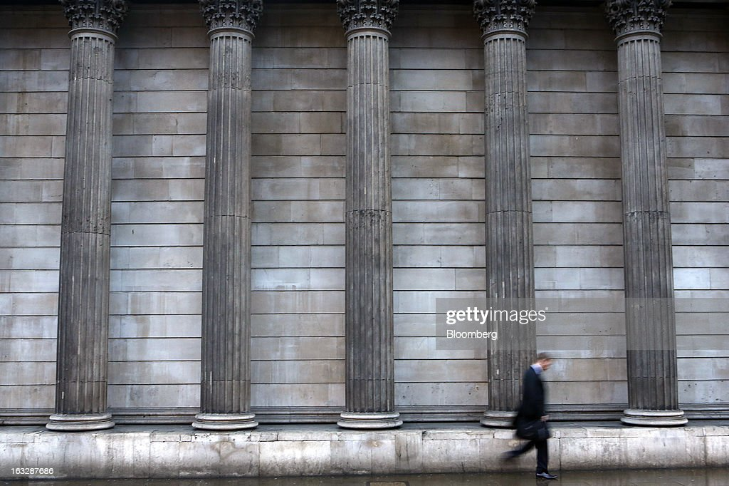 A pedestrian walks past decorative columns outside the Bank of England (BoE) in London, U.K., on Thursday, March 7, 2013. The pound dropped to its weakest level in more than 2 1/2 years versus the dollar before Bank of England policy makers announce their decision on whether they will add more stimulus to boost the U.K. economy. Photographer: Simon Dawson/Bloomberg via Getty Images