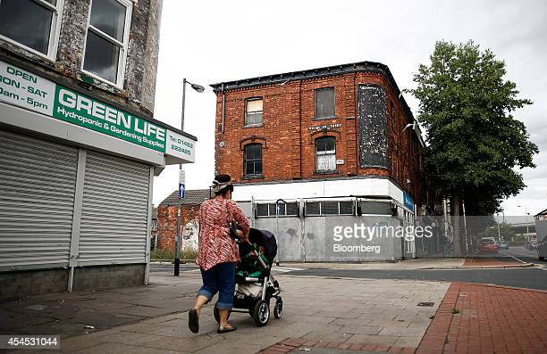A pedestrian walks past derelict shops in Hull UK on Friday Aug 22 2014 Hull with a population of about 250 has an unemployment rate of 135 percent...