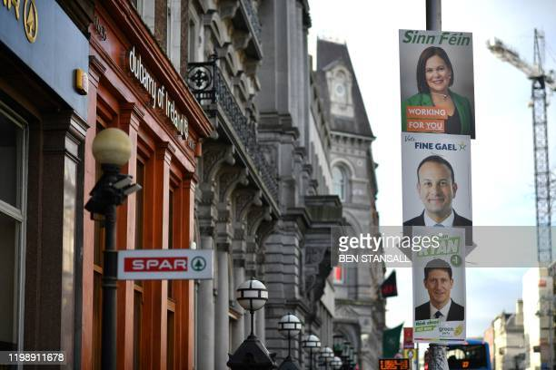 A pedestrian walks past election posters featuring Sinn Fein President Mary Lou McDonald Ireland's Prime minister and Fine Gael leader Leo Varadkar...