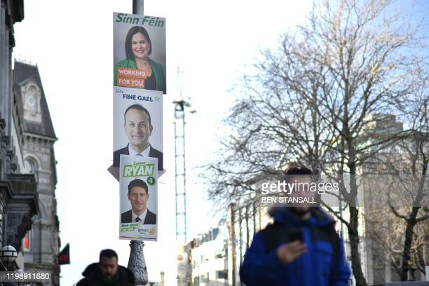 A pedestrian walks past election posters featuring Sinn Fein President Mary Lou McDonald Ireland's Prime minister and Fine Gael leader Leo Varadkar...