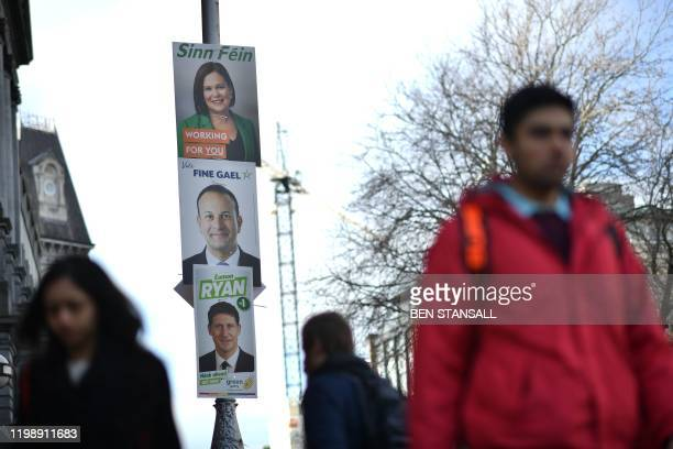 Pedestrian walks past election posters featuring Sinn Fein President Mary Lou McDonald , Ireland's Prime minister and Fine Gael leader Leo Varadkar...