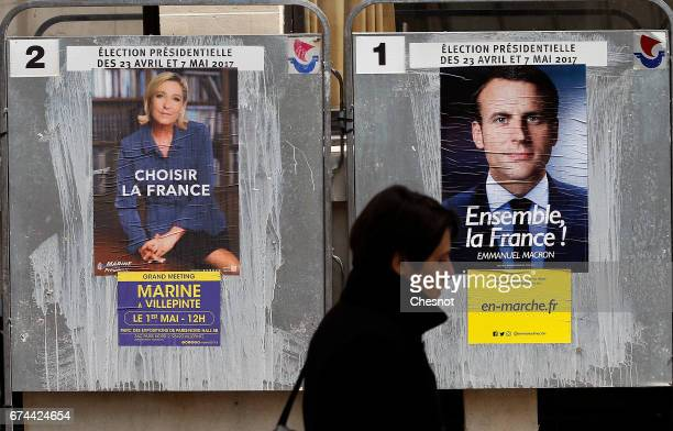 A pedestrian walks past electoral posters of French presidential election candidate for the En Marche movement Emmanuel Macron and French...