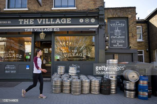 Pedestrian walks past empty beer barrels waiting to be collected, outside The Village Pub in Walthamstow, northeast London on April 6 as it restocks...