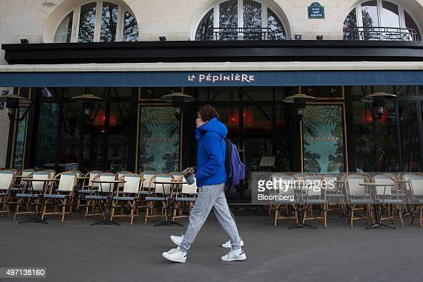 A pedestrian walks past empty tables at a cafe in Paris France on Saturday Nov 14 2015 French President Francois Hollande blamed Islamic State...