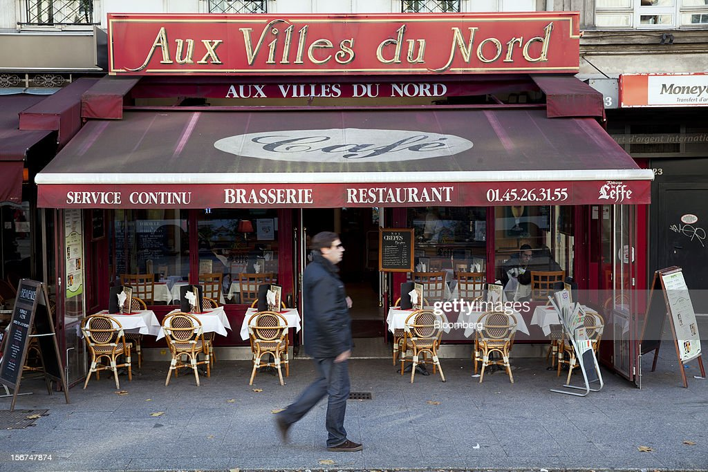 A pedestrian walks past empty tables outside the Aux Villes de Nord brasserie in Paris, France, on Tuesday, Nov. 20, 2012. France's government bonds fell, with 10-year yields rising the most in a month, after Moody's Investors Service lowered the nation's top credit rating, citing a worsening economic growth outlook. Photographer: Balint Porneczi/Bloomberg via Getty Images