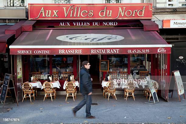 Pedestrian walks past empty tables outside the Aux Villes de Nord brasserie in Paris, France, on Tuesday, Nov. 20, 2012. France's government bonds...