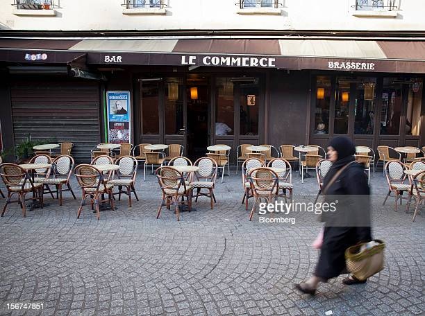 Pedestrian walks past empty tables outside the Le Commerce cafe in Paris, France, on Tuesday, Nov. 20, 2012. France's government bonds fell, with...