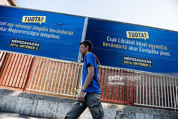 A pedestrian walks past government installed migration referendum billboard posters in Budapest Hungary on Thursday August 25 2016 Hungarians will...
