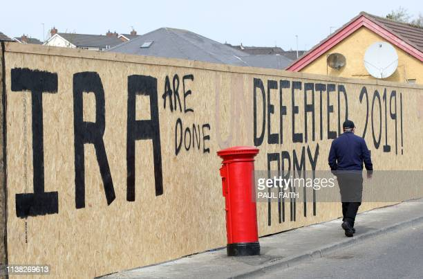A pedestrian walks past graffiti that has been amended to read IRA are done Defeated Army 2019 instead of IRA undefeated Army 2019 in the Creggan...