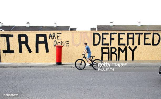 TOPSHOT A pedestrian walks past graffiti that has been amended to read IRA are done Defeated Army instead of IRA undefeated Army in the Creggan area...