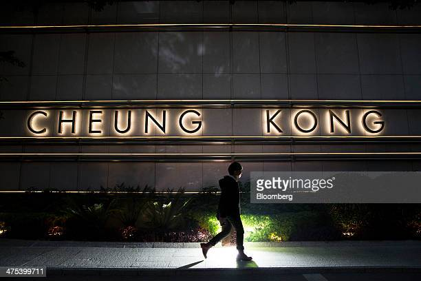 A pedestrian walks past illuminated signage for Cheung Kong Center which houses the headquarters for billionaire Li Kashing's Cheung Kong Holdings...