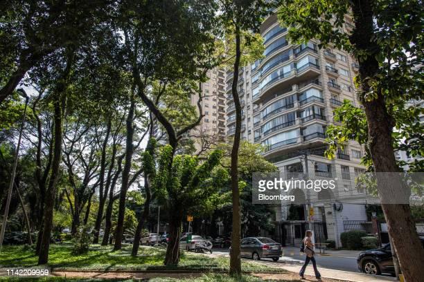Pedestrian walks past luxury apartment buildings in the Vila Nova Conceicao neighborhood of Sao Paulo, on Monday, May 6, 2019. The luxury...