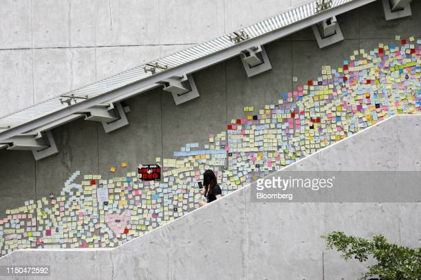 A pedestrian walks past messages posted to the Lennon Wall at the Central Government Offices in Hong Kong China on Tuesday June 18 2019 Hong Kong's...