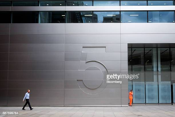 A pedestrian walks past No 5 Broadgate an office complex to be occupied by UBS AG as construction work nears completion in London UK on Tuesday Aug 9...