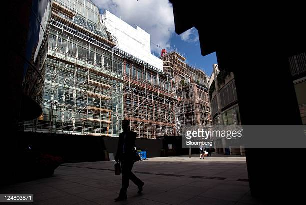 Pedestrian walks past number 4 Broadgate as construction work is underway on the new London headquarters for UBS AG at the site owned by British Land...