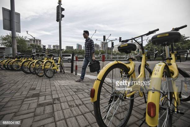 A pedestrian walks past parked Ofo Inc bicycles on a sidewalk in Shanghai China on Thursday May 25 2017 In China abicyclesharingphenomenon is...