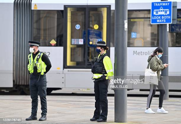 Pedestrian walks past police officers wearing face masks or coverings due to the COVID-19 pandemic, in Manchester, northwest England on October 20...