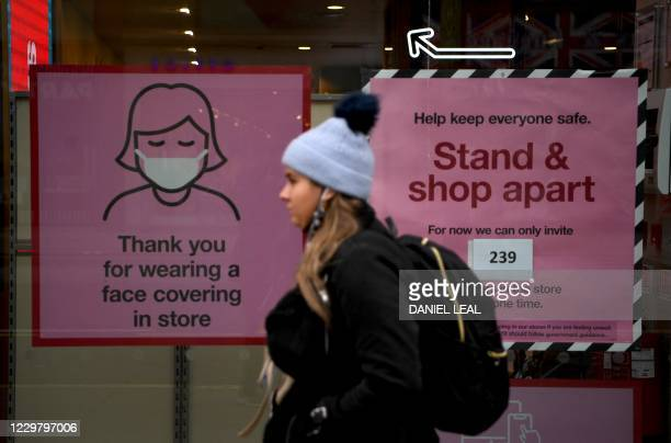 Pedestrian walks past posters advising customers to wear a face mask or covering due to the COVID-19 pandemic, as she walk past a temporarily...