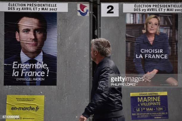 A pedestrian walks past posters of French presidential election candidate for the En Marche movement Emmanuel Macron and French presidential election...