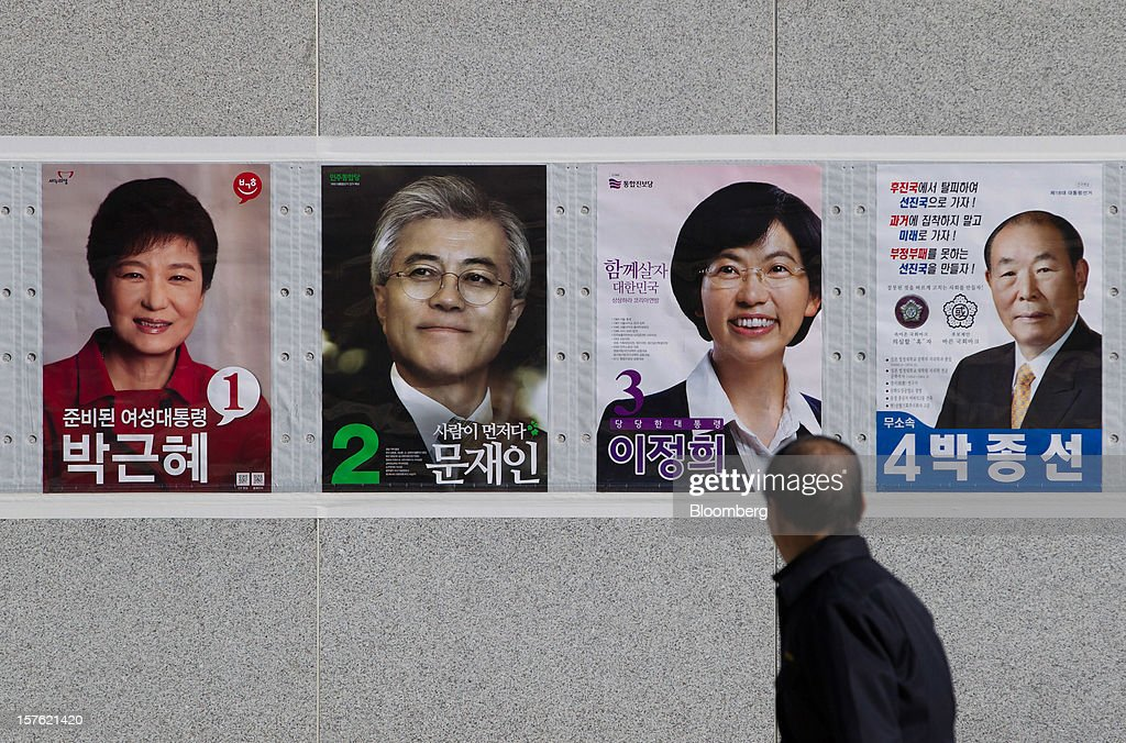 A pedestrian walks past posters of presidential candidates in Sejong, South Korea, on Tuesday, Dec. 4, 2012. The construction of Sejong City 120 kilometers (75 miles) south of the capital fulfills the vision of the late President Roh Moo Hyun, who pledged to reduce the dominance of Seoul and pump money into a region courted for its swing voters. Photographer: SeongJoon Cho/Bloomberg via Getty Images