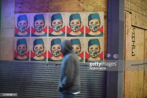 Pedestrian walks past posters showing a healthcare worker wearing a mask in Los Angeles, California as the state becomes the second in the US to...