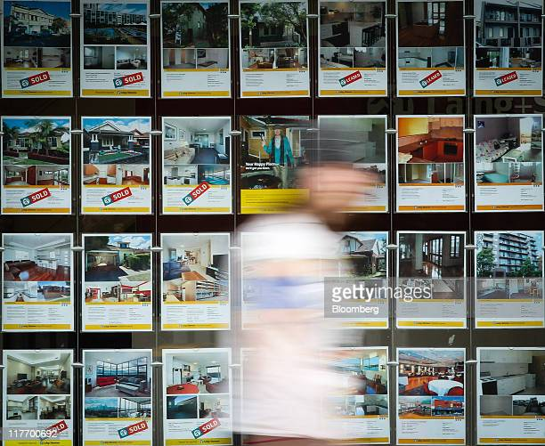 A pedestrian walks past property listings displayed in the window of a real estate agency in Sydney Australia on Tuesday June 28 2011 Australian home...