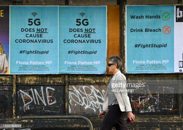 Pedestrian walks past public service announcement posters, negating a conspiracy that 5G telecommunications technology causes the coronavirus, amid...
