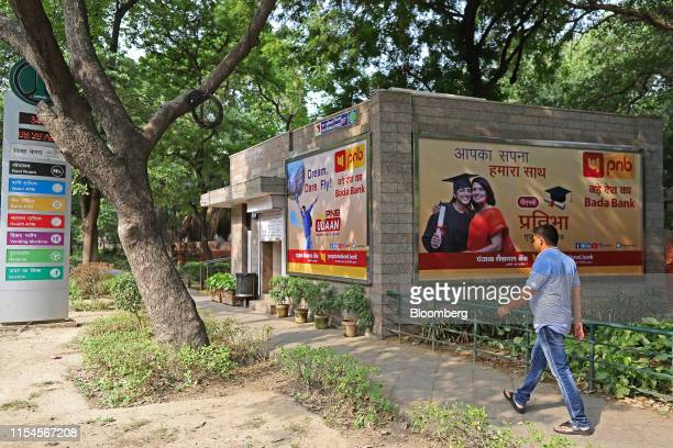 A pedestrian walks past Punjab National Bank billboard advertisements in New Delhi India on Monday July 8 2019 India's beleaguered staterun...
