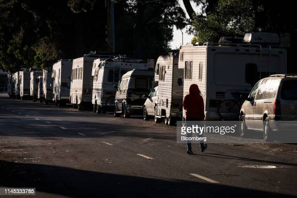 Pedestrian walks past recreational vehicles parked on Crisanto Avenue in Mountain View, California, U.S., on Wednesday, May 8, 2019. Mountain...