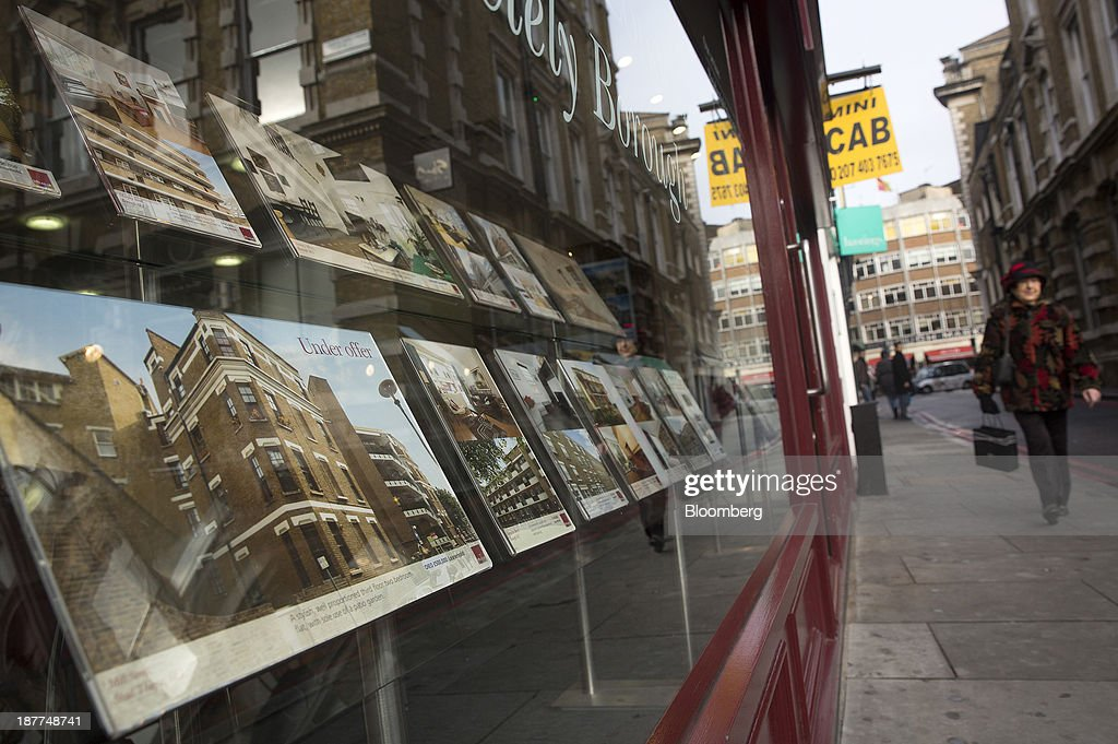 A pedestrian walks past residential properties displayed for sale in the window display of an estate agents in London, U.K., on Tuesday, Nov. 12, 2013. Under Bank of England Governor Mark Carney's forward-guidance policy, the central bank has pledged to not to withdraw stimulus at least until unemployment falls to 7 percent. Photographer: Simon Dawson/Bloomberg via Getty Images