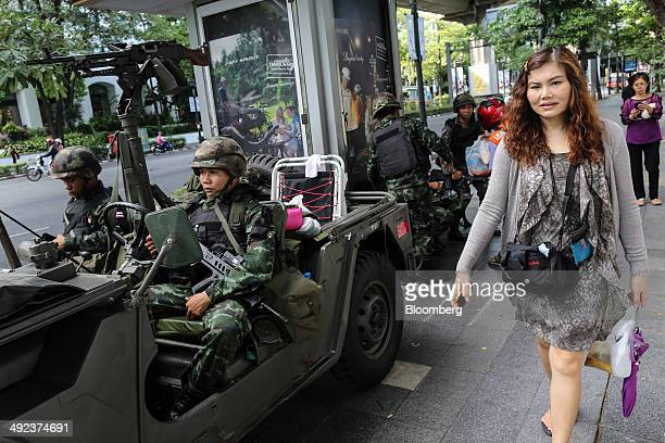 Pedestrian walks past Royal Thai Army soldiers stationed near luxury hotels on Ratchadamri Road in central Bangkok, Thailand, on Tuesday, May 20,...