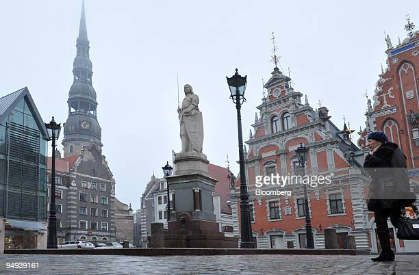 A pedestrian walks past Saint Roland's Statue and the House of the Blackheads in Riga Latvia on Friday February 27 2009 The Latvian central bank said...