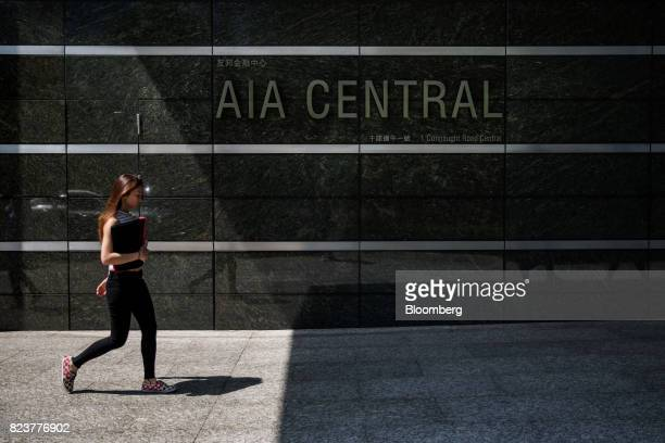 A pedestrian walks past signage for the AIA Central building which houses the headquarters of AIA Group Ltd in Hong Kong China on Friday July 28 2017...