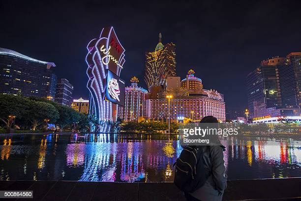 A pedestrian walks past signage for the Wynn Macau casino resort operated by Wynn Resorts Ltd front as the Casino Grand Lisboa operated by SJM...