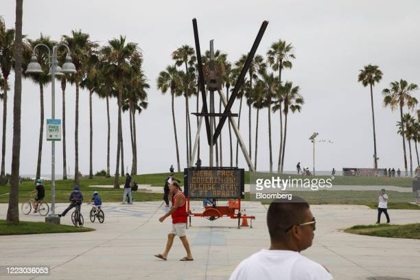 Pedestrian walks past social distancing signage at Venice Beach in Los Angeles, California, U.S., on Friday, June 26, 2020. California reported 5,349...