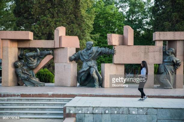 A pedestrian walks past statues in Dushanbe Tajikistan on Sunday April 22 2018 Flung into independence after the Soviet Union collapsed in 1991 the...