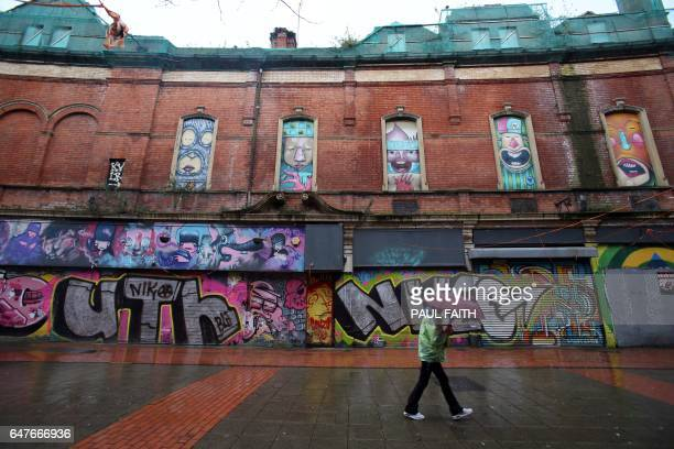 A pedestrian walks past street art in Belfast Northern Ireland on February 28 2017 For decades Belfast adorned its walls with huge community murals...