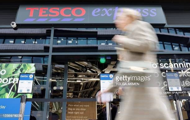 Pedestrian walks past supermarket chain Tesco's first check-out free food store in Holborn, central London, on October 19, 2021. - Britain's biggest...