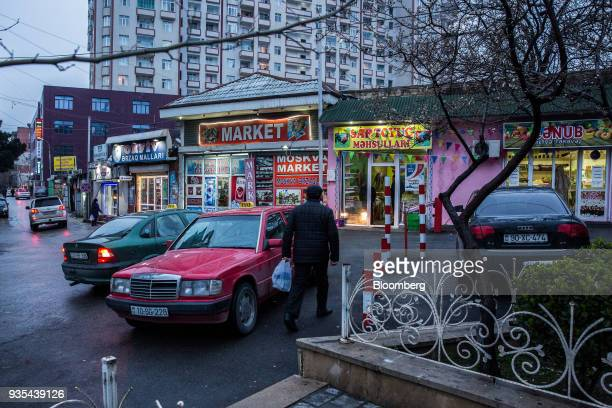 A pedestrian walks past taxis parked outside a row of stores in Baku Azerbaijan on Friday March 16 2018 Azerbaijan's economy barely returned to...