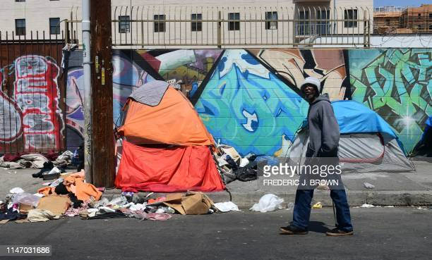 A pedestrian walks past tents and trash on a sidewalk in downtown Los Angeles on May 30 2019 The city of Los Angeles on May 29 agreed to allow...