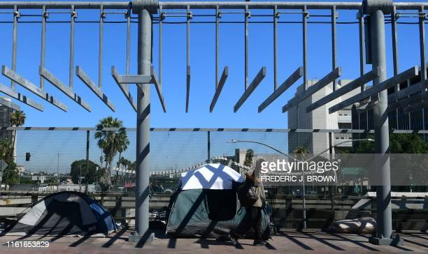 A pedestrian walks past tents housing homeless people in Los Angeles on August 14 2019 California has the nation's largest homeless population