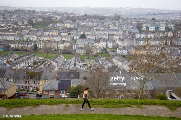 Pedestrian walks past terraced housing near the site of the Devonport freeport in Plymouth, U.K., on Thursday, March 4, 2021. U.K. Chancellor Rishi...